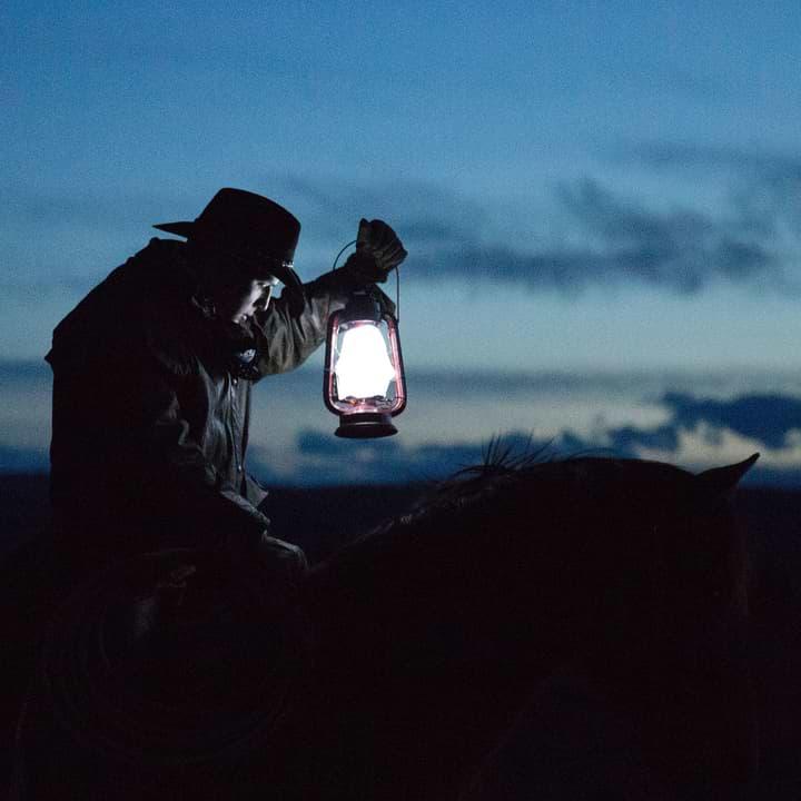 Cowboy riding horseback at night while holding up a lit lantern