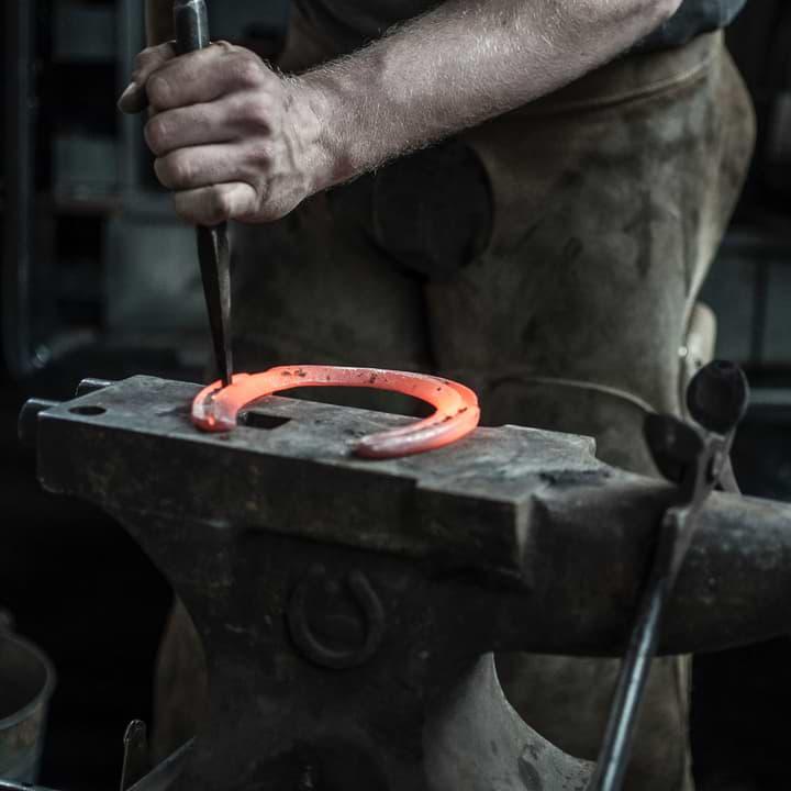 Blacksmith hammering red hot horseshoe